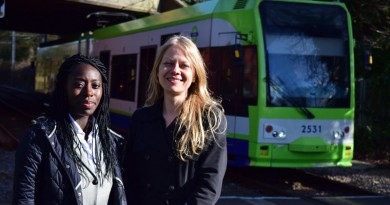 Sian Berry and Esther Obiri-Darko with a tram in Morden